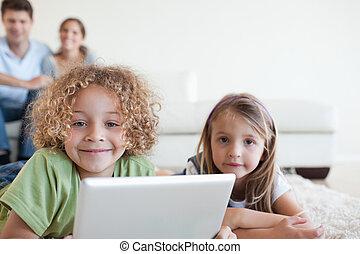 het glimlachen, kinderen, gebruik, een, tablet, computer, terwijl, hun, vrolijke , ouders, zijn, schouwend, in, hun, woonkamer