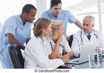 het glimlachen, medisch team, gebruikende laptop