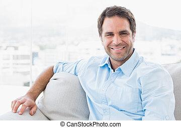 het glimlachen, mooi, bemannen zitting, op de bank, kijken naar van fototoestel