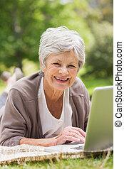 het glimlachen, oude vrouw, gebruikende laptop, op, park
