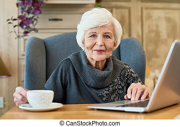 het glimlachen, oude vrouw, gebruikende laptop