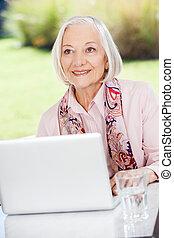het glimlachen, oudere vrouw, kijken weg, terwijl, gebruikende laptop, op, portiek