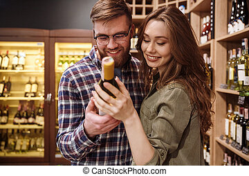 het glimlachen, paar, het kiezen van fles, van, wijntje