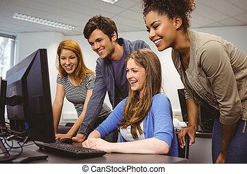het glimlachen, scholieren, zitting op het bureau, het gebruiken computer, samen