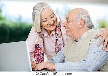 het glimlachen, senior koppel, beschouwende elkaar, terwijl, gebruikende laptop