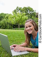 het glimlachen, tiener, kijken naar van het fototoestel, terwijl, gebruik, haar, draagbare computer