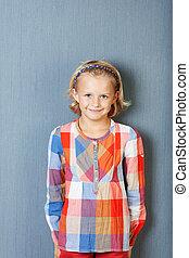 het glimlachen van het meisje, terwijl, staand, tegen, blauwe muur