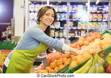 het glimlachen, verkoopster, schikken, sinaasappel, in, supermarkt
