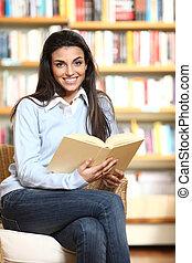 het glimlachen, vrouwelijke student, met, boek, in, handen, zitting als voorzitter, in, een, boekhandel, -, model, kijken naar, camera.