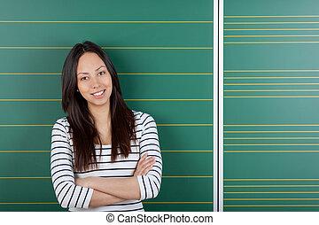 het glimlachen, vrouwelijke student, met, gekruiste armen