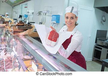 het glimlachen, vrouwlijk, slager, met, vlees, op, de, toonbank