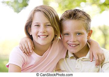 het glimlachen, zuster, buitenshuis, broer, zittende