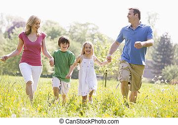 het lopen van de familie, buitenshuis, holdingshanden, het glimlachen
