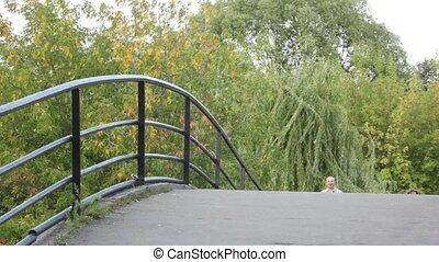 het lopen van de familie, op, brug, in park, naar de camera
