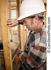 het meten, de arbeider van de bouw