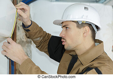 het meten, muur, de arbeider van de bouw, jonge