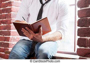 het noteren, zijn, thoughts., close-up, van, jonge man, in, hemd en meren, schrijvende , iets, in, opmerking blok, terwijl, zittende , op het venster, sill