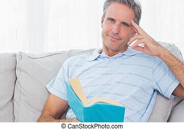 het ontspannen van de mens, op, zijn, bankstel, met, een, boek, kijken naar van fototoestel