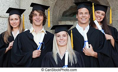 het poseren, close-up, vrolijke , vijf, afgestudeerdeen