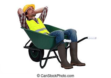 het rusten, de arbeider van de bouw, kruiwagen