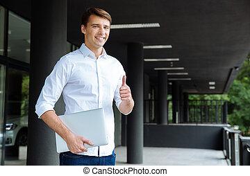 het tonen, op, duimen, vasthouden, zakenman, het glimlachen, draagbare computer
