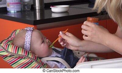 het voeden, moeder, baby meisje, lepel