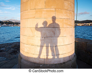 Heterosexual couple makes funy shadows on wall