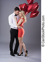 Heterosexual couple with red heartshape balloons