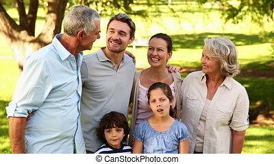 heureux, étendu famille, sourire, appareil-photo