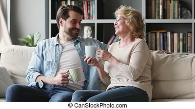 heureux, conversation, générations, famille, sofa, deux, asseoir, thé, boire