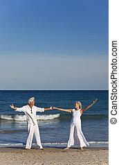 heureux, couples aînés, danse, tenant mains, sur, a, plage tropicale