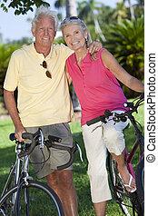 heureux, couples aînés, sur, bicycles, dans, parc vert