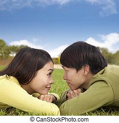 heureux, couples asiatiques, coucher herbe, à, nuage, fond