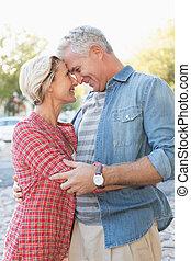 heureux, couples mûrs, étreindre, dans ville
