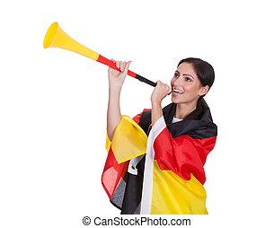 heureux, femme, allemand, supporter, souffler, vuvuzela