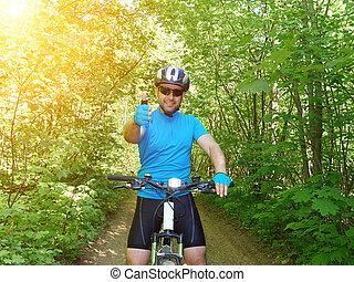 heureux, homme, équitation, a, vélo tout terrain, dans, les, vert, woods.