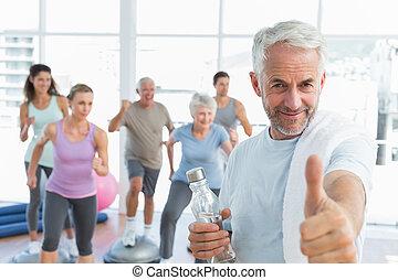 heureux, homme aîné, faire gestes, pouces haut, à, gens, exercisme, dans, les, fond, à, fitness, studio