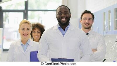 heureux, hommes, moderne, américain, scientifique, africaine, laboratoire, sourire, équipe, divers, chercheurs, femmes
