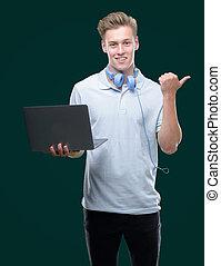 heureux, indiquer haut, ordinateur portable, jeune, main, doigt, blonds, homme, utilisation, face souriant, beau