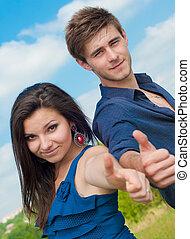 heureux, jeune couple, projection, pouces haut