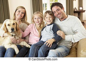 heureux, jeune famille, s'asseoir sofa, tenue, a, chien