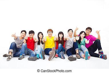 heureux, jeune, groupe, reposer ensemble, à, pouce haut