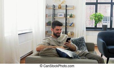 heureux, smartphone, homme, maison