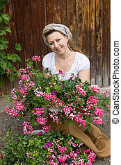 A young peasant woman kneeling on the ground with a pot full of geraniums