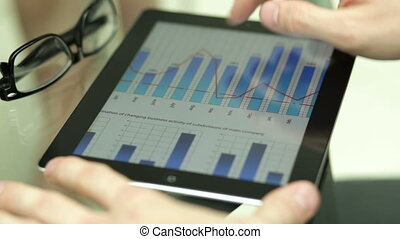 Hi-tech analysis - Office worker using a touchpad to analyze...