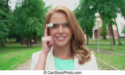 Hi-Tech Device - Girl walking leisurely through the park and...