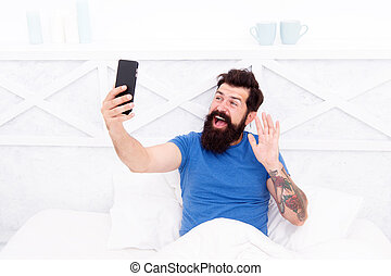 Hi there. Bearded man use smartphone in bed. Mobile technology. New technology for mobile lifestyle. Modern life. Wireless communication technology in home. Take advantage of mobile technology