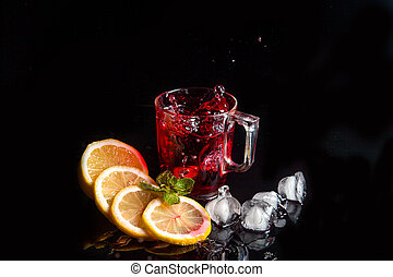 Hibiscus cold tea splash from the fallen ice cube into glass with beverage isolated on black background.