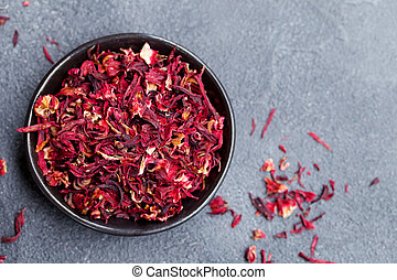 Hibiscus flower tea in black bowl on grey stone background. Copy space. Top view.