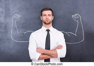 Hidden possibilities. Handsome young man in shirt and tie looking at camera and keeping arms crossed while standing against chalk drawing of muscular arms
